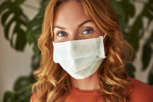 Portrait of red-haired woman wearing a protective mask at home - JHAF00079