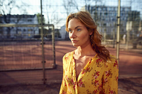 Portrait of red-haired woman at football ground - JHAF00097