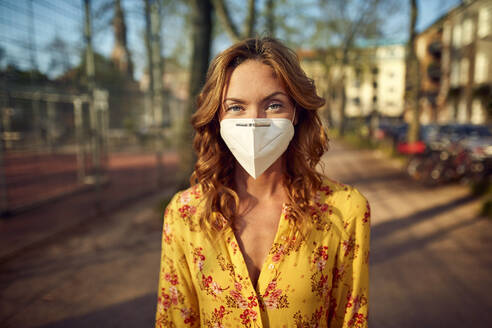 Red-haired woman wearing a FFP2 face mask in the city - JHAF00100