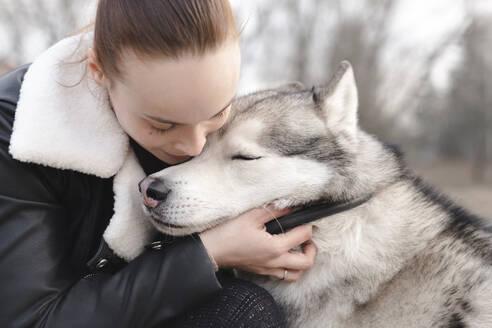 Woman cuddling her husky - EYAF01038