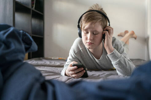 Portrait of boy with headphones lying on bed looking at cell phone - VPIF02331