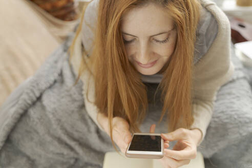 Young woman lying on blanket using smartphone - AFVF06006