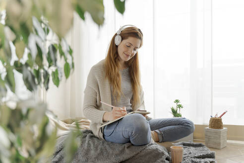 Young woman wearing headphones and taking notes at home - AFVF06012