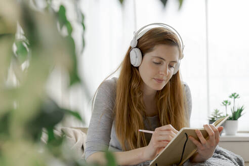 Young woman wearing headphones and taking notes at home - AFVF06021
