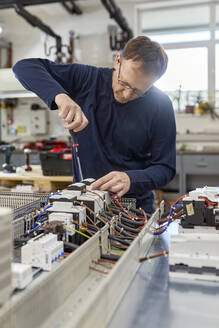 Electrician working on circuitry in workshop - ZEDF03216
