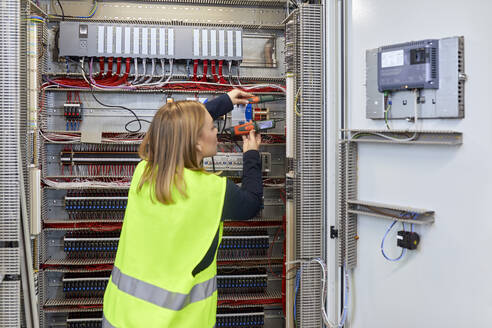 Female electrician working with voltmeter at fuse box - ZEDF03231
