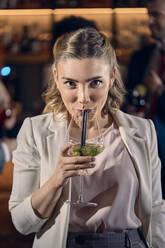 Portrait of a young woman having a cocktail in a bar - ZEDF03293