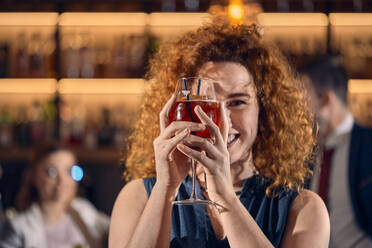 Portrait of a happy young woman holding a cocktail glass in a bar - ZEDF03299