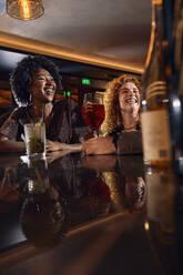 Happy friends socializing in a bar - ZEDF03308
