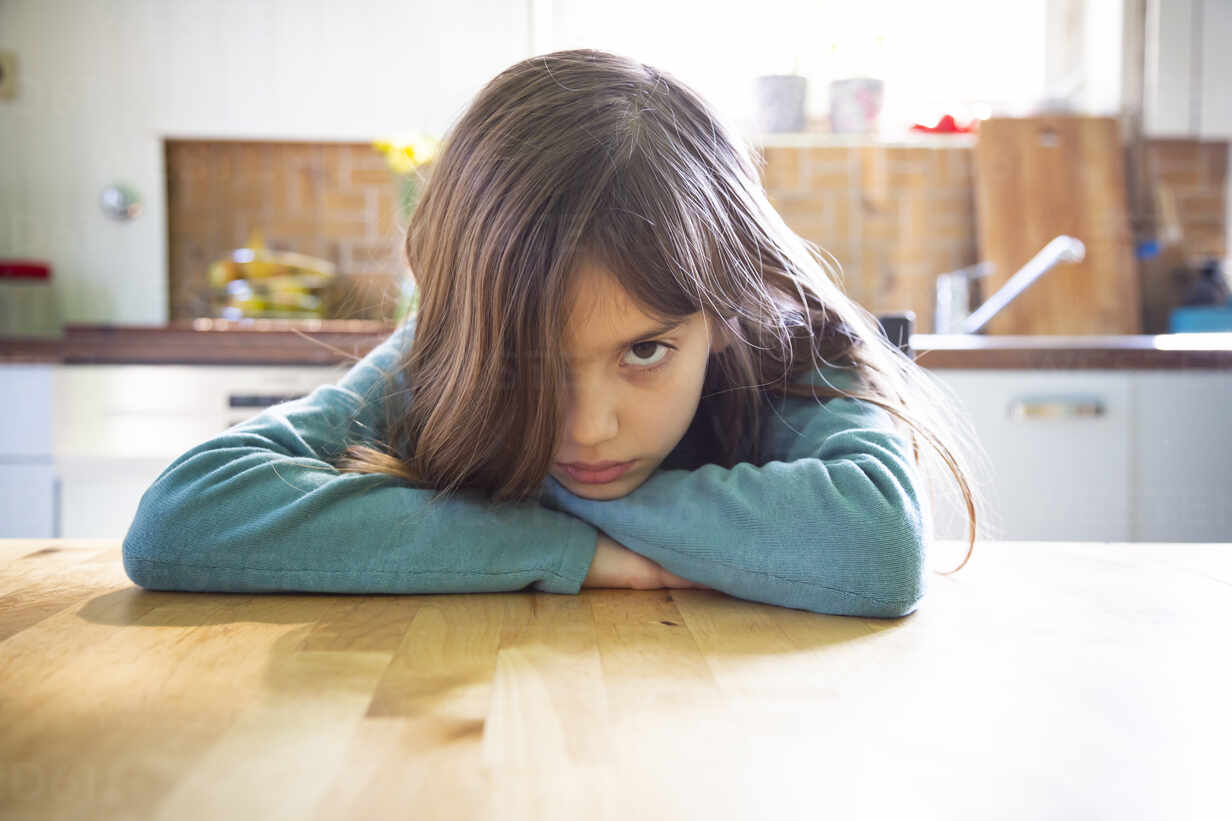 Annoyed Girl Sitting In Kitchen Leaning On Table Stockphoto