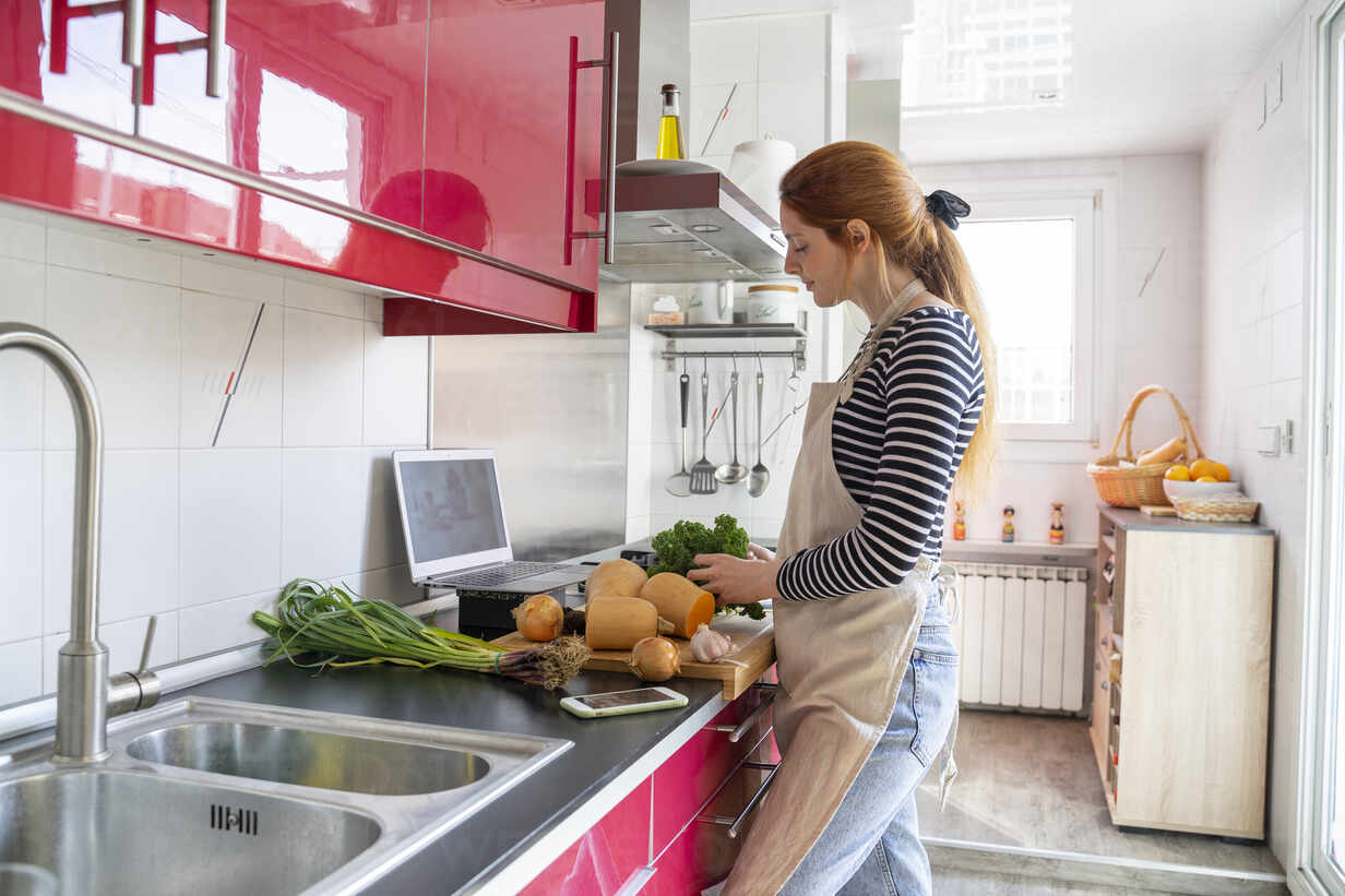 Young Woman Havig A Video Chat While Cooking A Healthy Meal Stockphoto