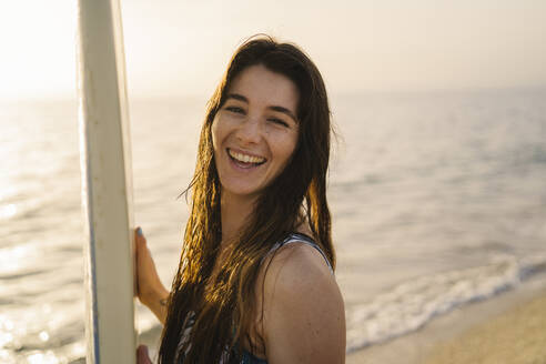 Portrait of laughing young woman with surfboard on the beach, Almeria, Spain - MPPF00826