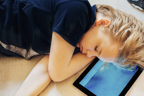Boy lying on tablet on couch taking a nap - MJF02450