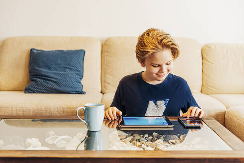Boy using smartphone and tablet in living room at home - MJF02453