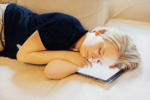 Boy lying on tablet at home taking a nap - MJF02480