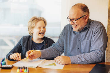 Happy father and son doing homework at desk - MJF02495