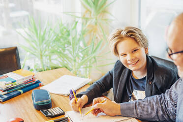Portrait of smiling boy with father doing homework at desk - MJF02498