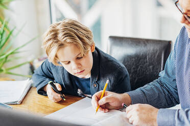 Father helping son doing homework at desk - MJF02507