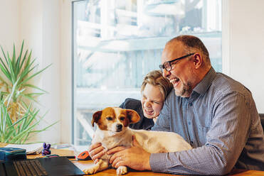 Happy father and son at home with dog on desk - MJF02510