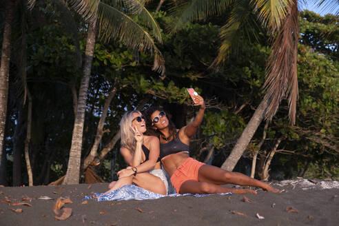 Two happy women taking selfie on the beach, Costa Rica - AMUF00066