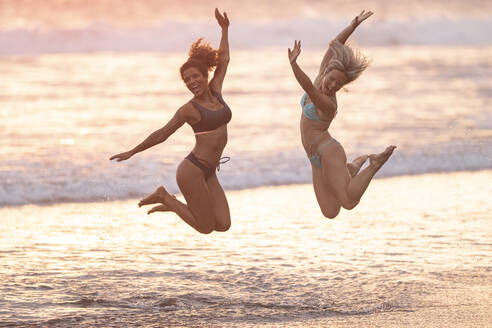 Two carefree women jumping on the beach, Costa Rica - AMUF00072