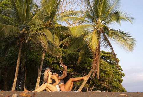 Two women reading a book on the beach, Costa Rica - AMUF00078