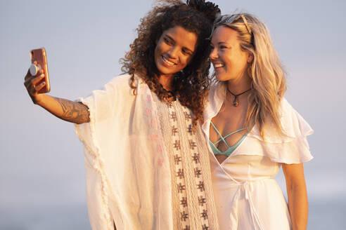 Two happy women taking selfie on the beach, Costa Rica - AMUF00084