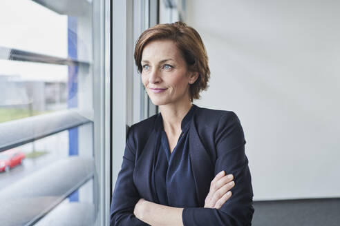 Portrait of confident businesswoman looking out of window - RORF02119