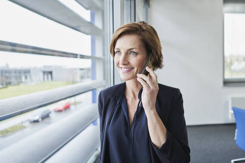 Smiling businesswoman on the phone at the window - RORF02122