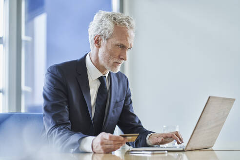 Businessman holding credit card and using laptop at desk in office - RORF02146
