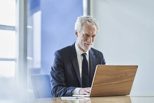 Confident businessman using laptop at desk in office - RORF02149