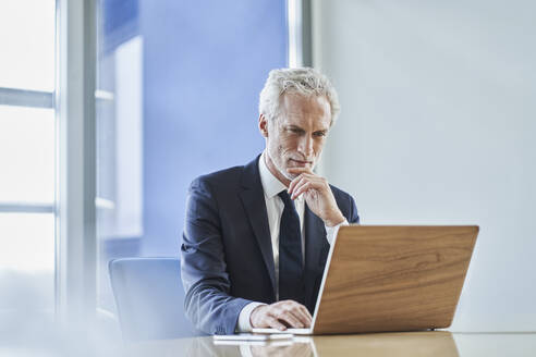 Focused businessman using laptop at desk in office - RORF02152