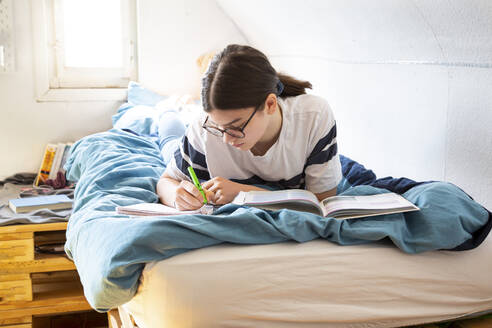 Girl lying on bed doing homework - LVF08816