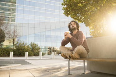 Portrait of bearded man relaxing on bench with coffee to go at sunset - KIJF02974