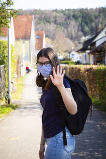 Teenage girl on her way to school, wearing face mask - LVF08820