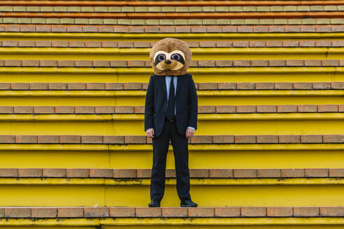 Businessman in black suit with meerkat mask standing on stairs - XLGF00029