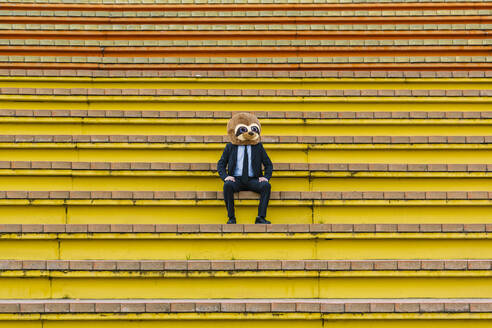 Businessman in black suit with meerkat mask sitting on stairs - XLGF00032