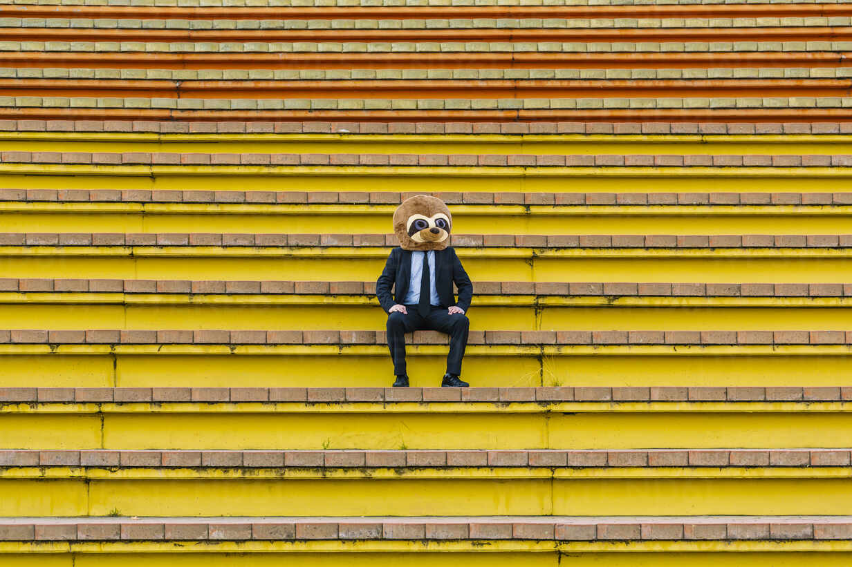 Businessman in black suit with meerkat mask sitting on stairs - XLGF00032 - Xavier Lorenzo/Westend61
