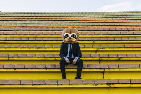 Businessman in black suit with meerkat mask sitting on stairs - XLGF00035