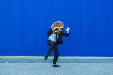 Businessman in black suit with meerkat mask dancing in front of blue wall - XLGF00041