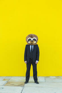 Businessman in black suit with meerkat mask standing in front of yellow wall - XLGF00044