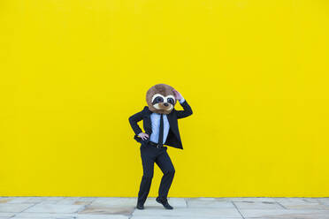 Businessman in black suit with meerkat mask dancing in front of yellow wall - XLGF00047