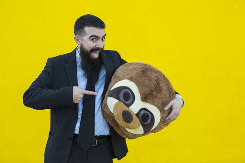 Portrait of businessman in black suit with meerkat mask in front of yellow wall - XLGF00050