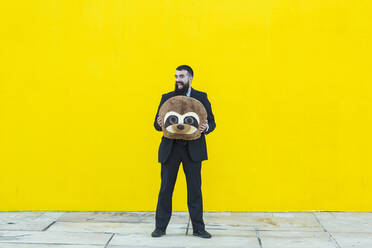 Portrait of businessman in black suit holding meerkat mask in front of yellow wall - XLGF00053