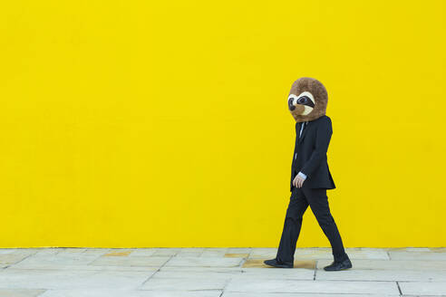 Businessman in black suit with meerkat mask walking in front of yellow wall - XLGF00056