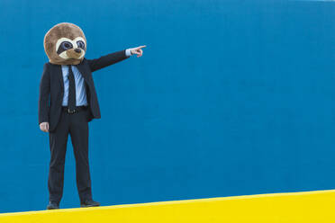Portrait of businessman in black suit with meerkat mask standing on yellow wall in front of blue background - XLGF00062