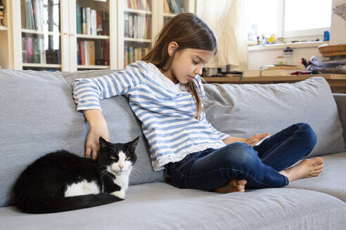 Girl sitting on couch using digital tablet while stroking cat - LVF08826