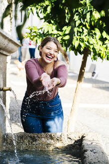 Carefree woman at a water well in the city - DGOF00808