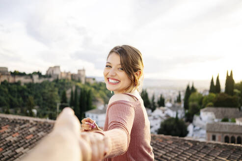 Portrait of happy woman holding hands with Alhambra in background, Granada, Spain - DGOF00841