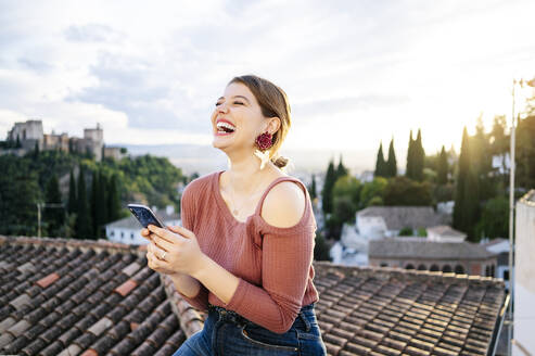 Portrait of happy woman with Alhambra in background, Granada, Spain - DGOF00844